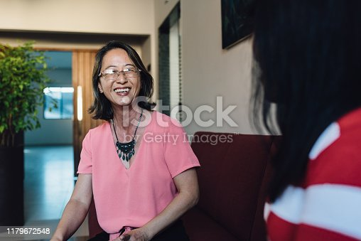 Oriental mature woman talking at home