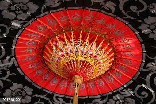 Traditional Asian handcraft paper umbrella in vivid red with black border found at Bo Sang Handicraft Centre, Chiang Mai, Thailand.