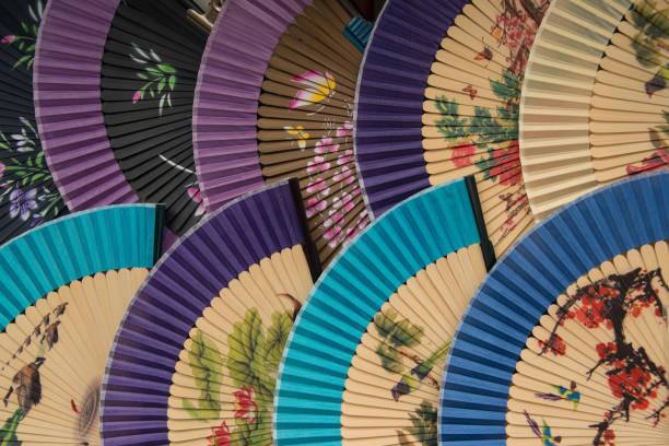 orientalische seide handfächer mit blumendesign - japanischer fächer stock-fotos und bilder