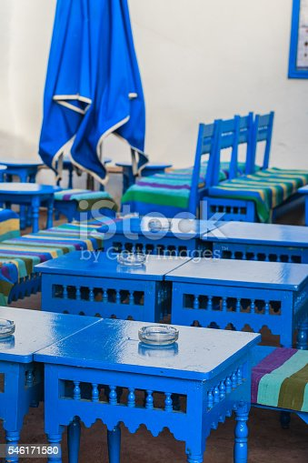 Oriental style restaurant with blue wooden tables and benches