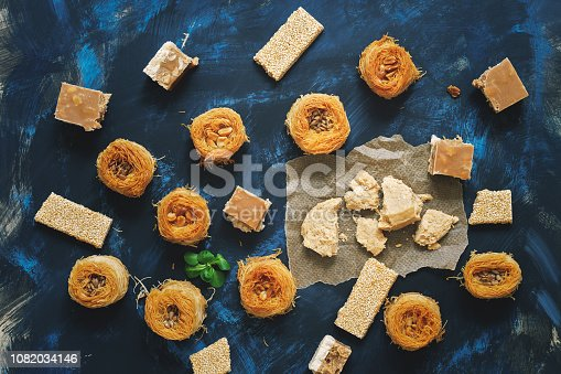 istock Oriental sweets, baklava, halva, sesame with honey, sherbet on a blue background. Arabic sweets.Top view 1082034146