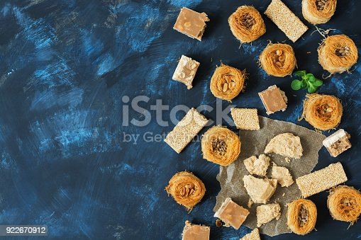 istock Oriental sweets, baklava, halva, sesame with honey, sherbet on a blue background. Top view, space for text. 922670912