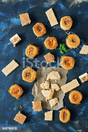 istock Oriental sweets, baklava, halva, sesame with honey, sherbet on a blue background. Arabic sweets.Top view 945789578