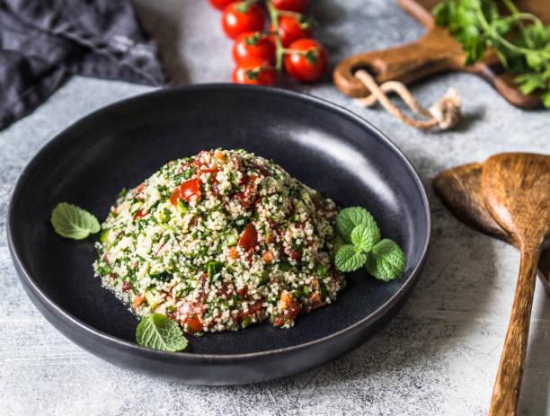 orientalischer taboulé salat mit couscous, gemüse und kräutern in einer schwarzen schale auf einem grauen hintergrund - couscous salat minze stock-fotos und bilder