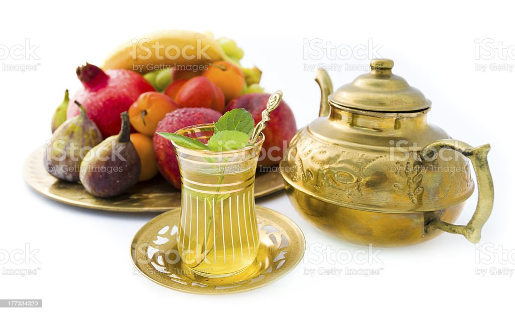 Oriental tea set with fruits on golden plate royalty-free stock photo