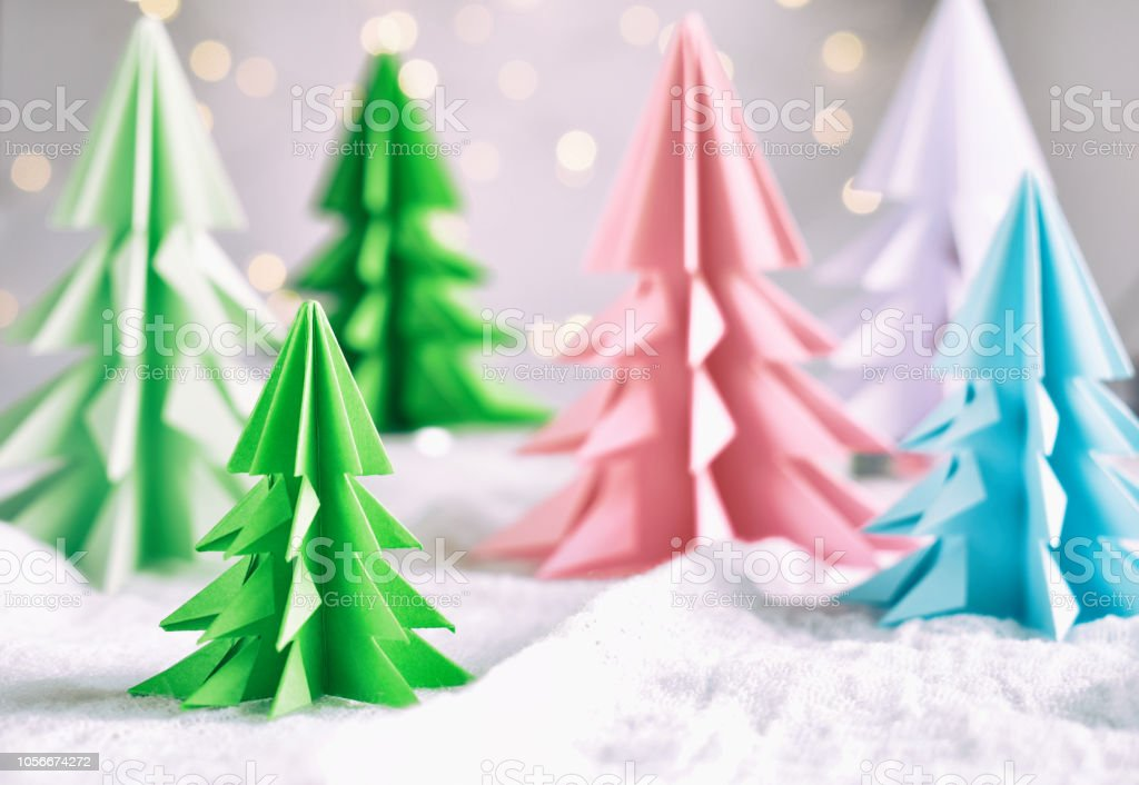 Origami 3D Xmas tree from paper on white background and bokeh lights. Merry Christmas and New Year card. Paper art style. Copy space. Selective focus stock photo