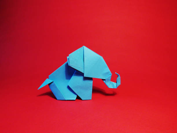 origami blue elephant on red background - origami elefant stock-fotos und bilder