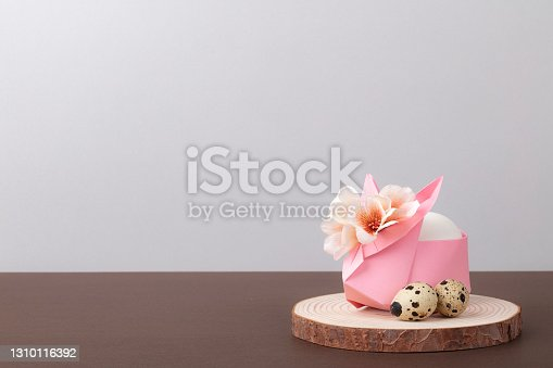 Origami bunny with flowers and quail eggs,  Happy Easter Day, holiday greetings, agriculture, Spring Festival concept. Minimalist style. Blank space.