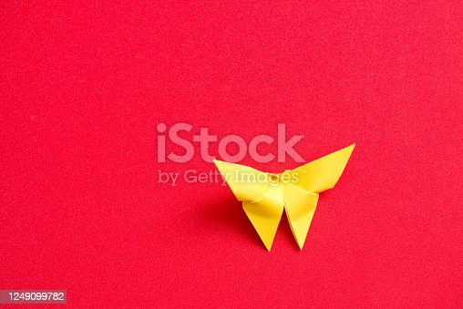 Origami yellow butterfly on a red background