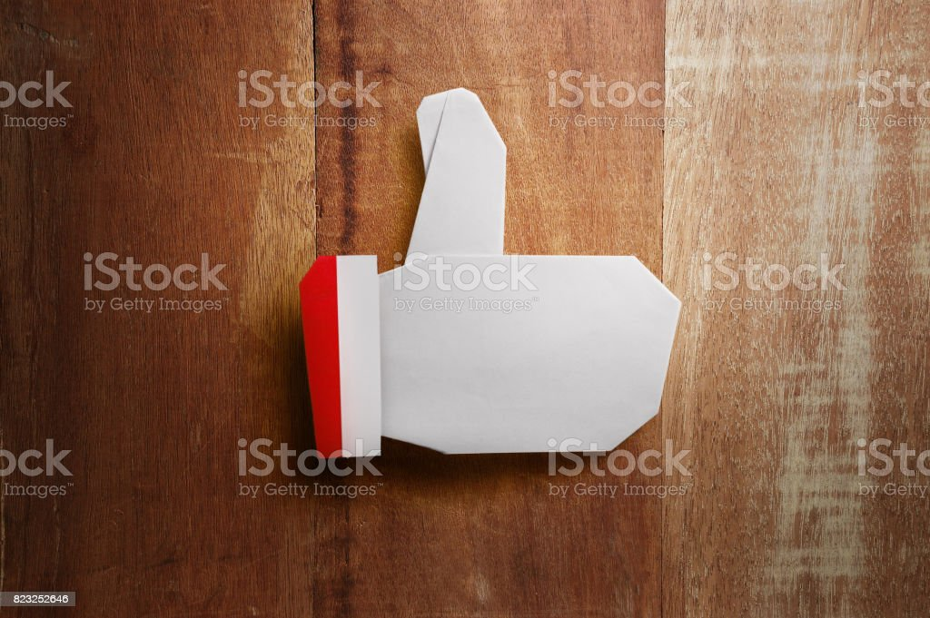 Origami Christmas thumb up paper craft on wooden background stock photo