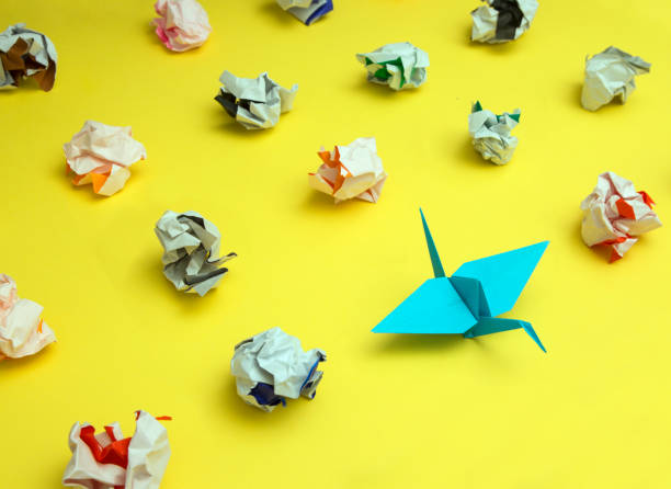 Origami Crane Surrounded by Crumpled Paper Origami bird stands out from the crowd surrounded by failed attempts persistence stock pictures, royalty-free photos & images