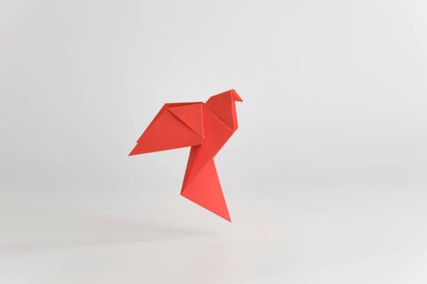 colombe en origami faite de papier rouge sur fond blanc uni. concept minimal. - origami photos et images de collection