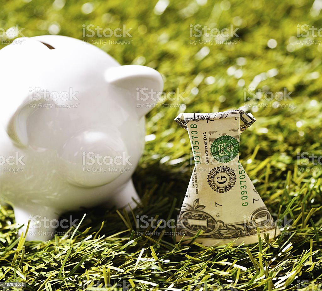 Origami dress made from dollar bill with piggybank on grass royalty-free stock photo