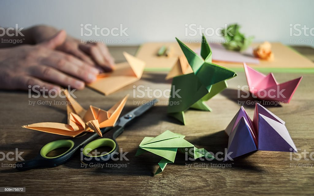 Origami figures on the table with hands in the backdground. stock photo