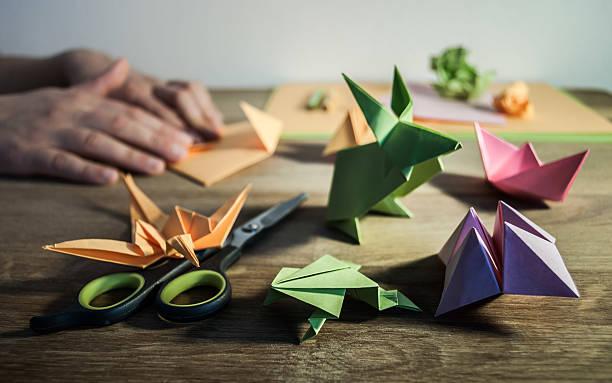 origami chiffres sur la tableau avec les mains dans la backdground. - origami photos et images de collection