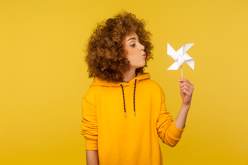 Origami hand mill. Portrait of carefree childish curly-haired woman in hoodie blowing at paper windmill