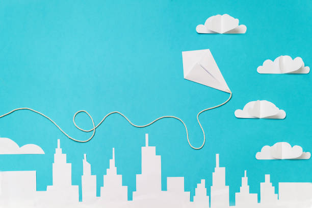 Origami kite flying trough paper cut clouds and a city silhouette. Paper cut banner template with copy space. stock photo
