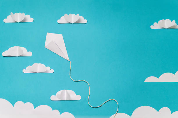Origami kite in sky with clouds. Creative concept for banner/landing/background designs. stock photo
