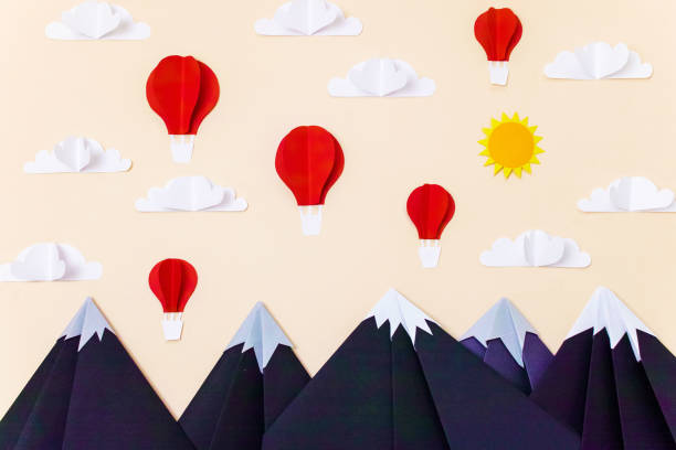 Origami mountain landscape with hot air balloons, 3d clouds and sun. Creative composition for banner/landing page/background stock photo