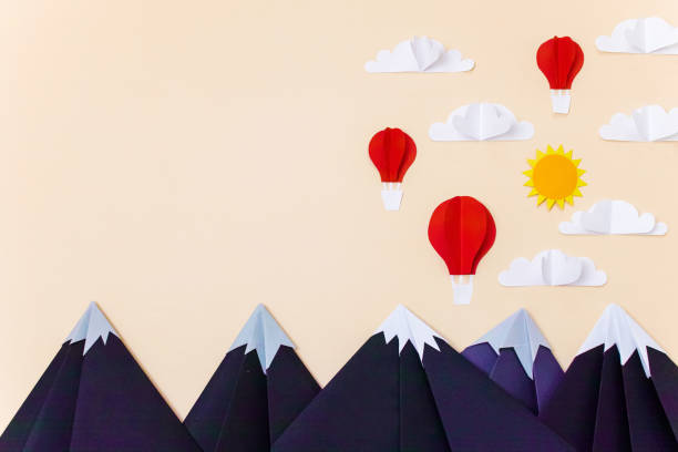 Origami mountains with hot air balloons, 3d clouds and sun. Creative composition for banner/landing page/background stock photo