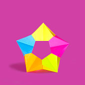Origami multicolored star on pink background. Paper art and craft. Trendy hobby. Minimal decorative concept