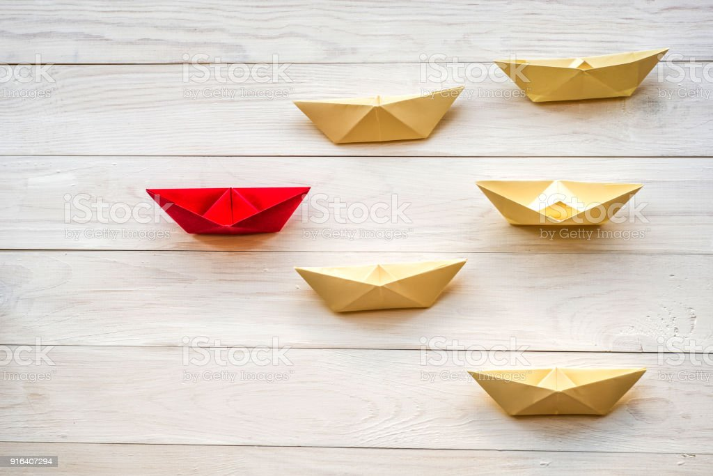 leadership concept. origami paper ships following a red boat leader...