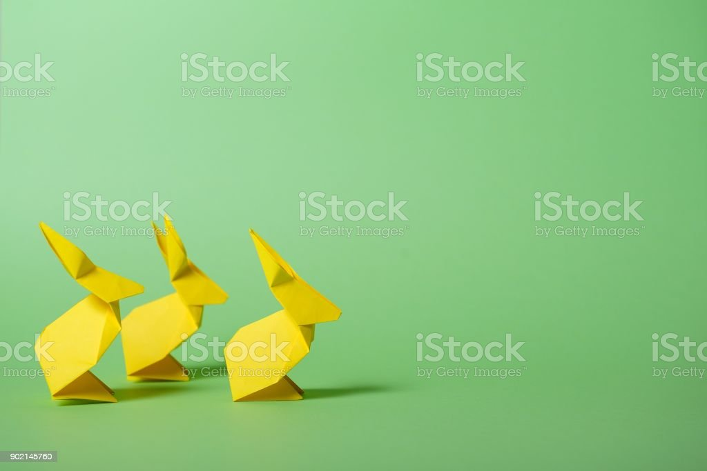 Origami paper colorful bunnies on green background. Easter ideas. Space for text. stock photo