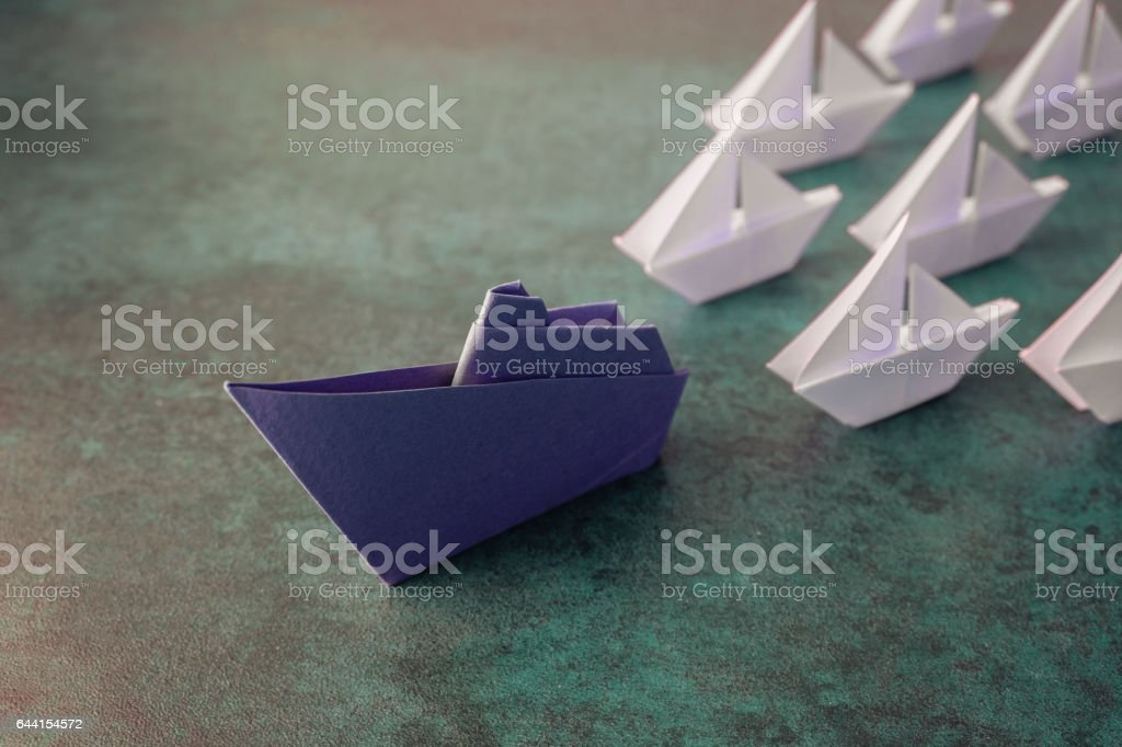Origami paper ship with small sailboats, leadership concept, toning stock photo