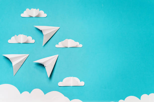 3 origami planes and paper cut sky with clouds. Craft objects for banners/landing pages/backgrounds design with copy space. stock photo