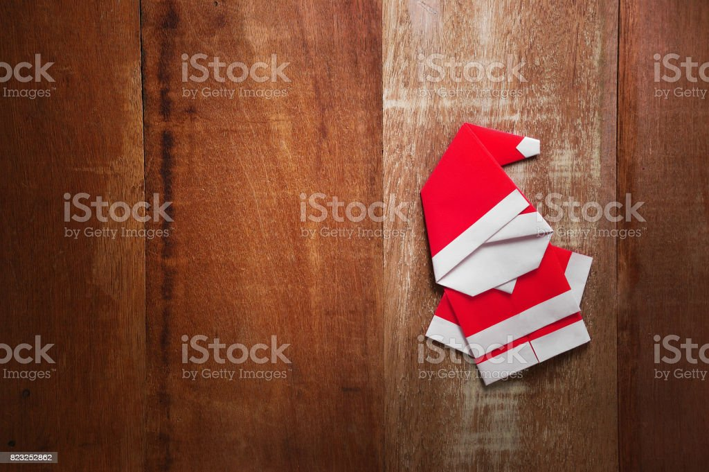 Origami Santa claus paper craft on wooden background stock photo