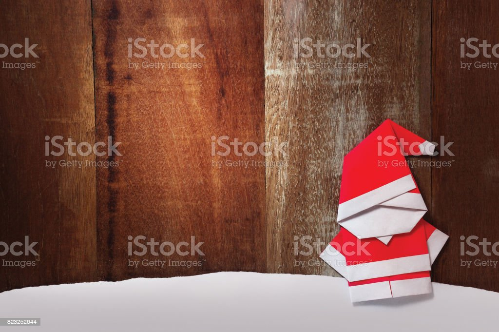 Origami Santa claus paper craft stand wooden background stock photo