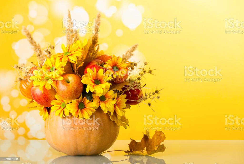 Original bouquet of apples, flowers and ears of corn in the pumpkin, on bright yellow stock photo