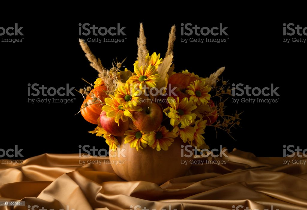 Original composition in a pumpkin on beige silk fabric, isolated on black stock photo