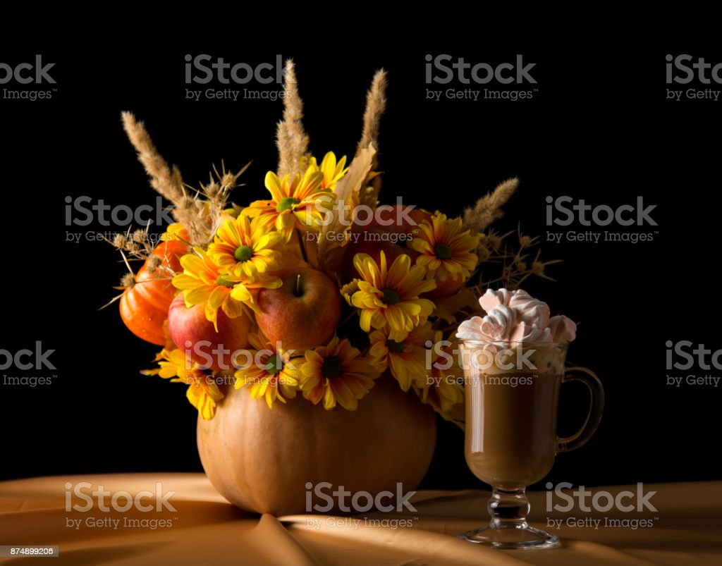 Original composition in the pumpkin, nearby cup of cappuccino with marshmallows, isolated on black stock photo