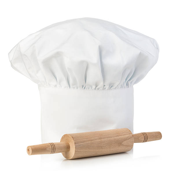 Original cooks cap with wooden rolling-pin. Chef's hat close-up isolated. stock photo