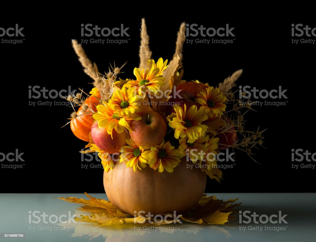 Original pumpkin vase with fruits and flowers stands on autumn leaves, isolated on black stock photo