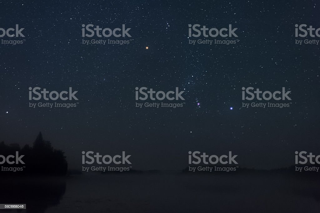 Orion constellation above misty lake stock photo