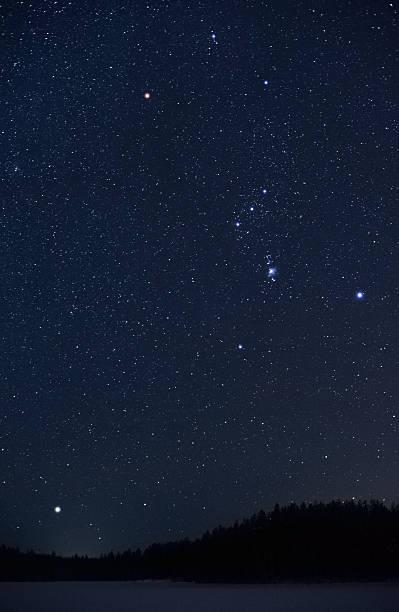 Orion constellation and Sirius rising above horizon stock photo