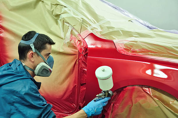 orker painting a car. - auto body repair stock photos and pictures