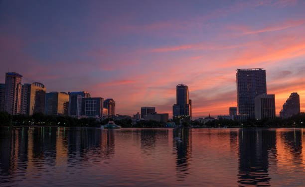 Orlando Florida Downtown Skyline During Vibrant Sunset Over Lake Eola stock photo