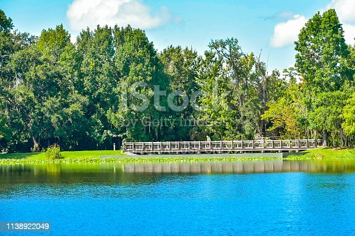 Orlando, Florida. January 15, 2019 . Beautiful natural scenery with autumn forest, wood bridge and blue lake at Celebration Town in Kissimmee area.