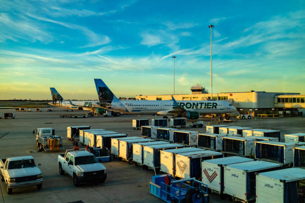 Orlando, Florida, USA - Two Frontier Airlines Airplanes Being Readied For Departure At Orlando International Airport At Almost Sunset Time. stock photo