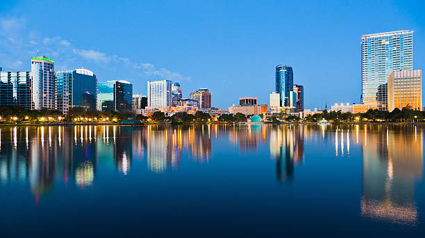 orlando skyline at dusk seen from lake eola - orlando florida photos stock photos and pictures