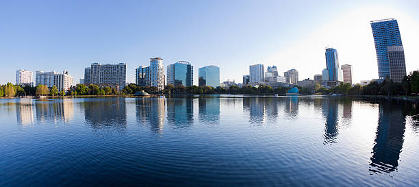 orlando skyline at sunrise seen from lake eola - orlando florida photos stock photos and pictures