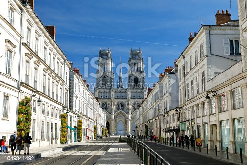 Orleans, France - September 29, 2018. Facade of the Cathedral of the Holy Cross (Cathédrale Sainte-Croix d'Orléans). Central perspective image - Joan of Arc Street (Avenue Jeanne d'Arc) with residential buildings left and right hand side. A few people in the streets.
