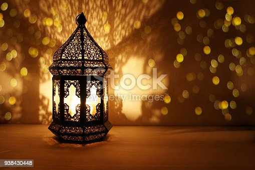 istock Ornamental Arabic lantern with burning candle glowing at night and glittering golden bokeh lights. Festive greeting card, invitation for Muslim holy month Ramadan Kareem. Dark background 938430448