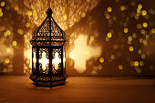Ornamental Arabic lantern with burning candle glowing at night and glittering golden bokeh lights. Festive greeting card, invitation for Muslim holy month Ramadan Kareem. Dark background