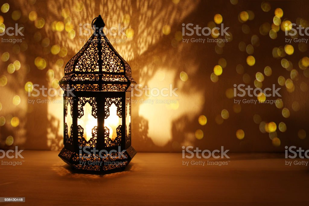 Ornamental Arabic lantern with burning candle glowing at night and glittering golden bokeh lights. Festive greeting card, invitation for Muslim holy month Ramadan Kareem. Dark background stock photo