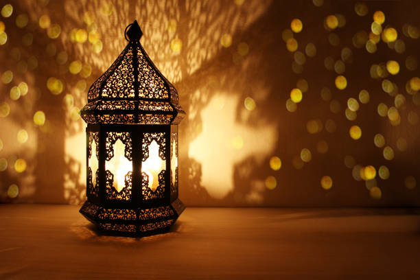 ornamental arabic lantern with burning candle glowing at night and glittering golden bokeh lights. festive greeting card, invitation for muslim holy month ramadan kareem. dark background - wschód zdjęcia i obrazy z banku zdjęć