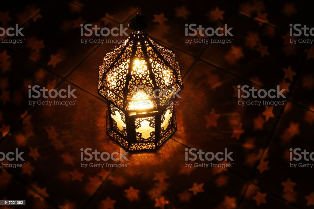 Ornamental Arabic lantern with burning candle glowing at night and glittering stars shaped bokeh lights. Festive greeting card, invitation for Muslim holy month Ramadan Kareem. Dark background. Top view. stock photo